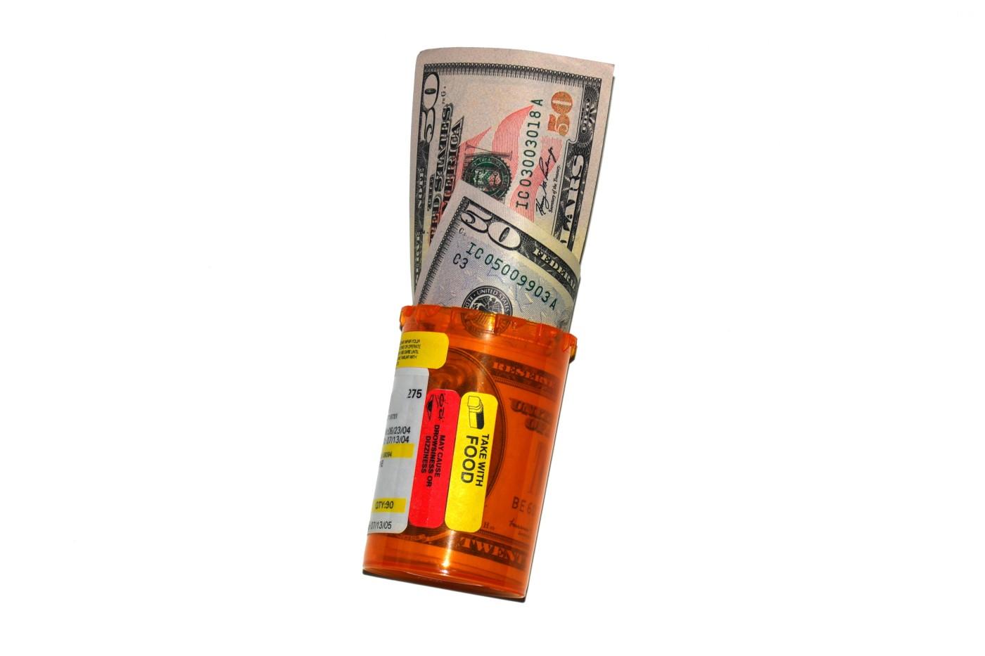Image of prescription bottle with money in it.