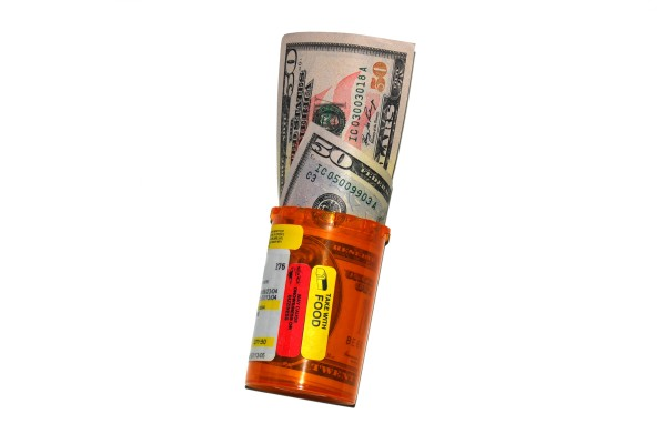 Image of prescription bottle with money in it.